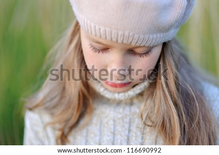 Portrait of a Girl. The child looks down. Long eyelashes. - stock photo
