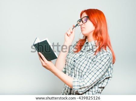 portrait of a girl thinking a notebook, red hair wearing glasses, isolated on a gray background - stock photo