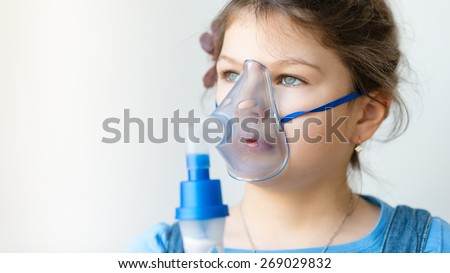 Portrait of a girl using asthma inhaler. Girl with Asthma Allergy problems making inhalation with mask on her face during Asthma attack - stock photo