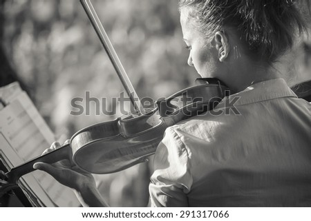 Portrait of a girl violinist, played in the orchestra in the summer in the open air - stock photo