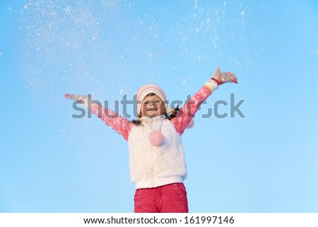 portrait of a girl walking around outdoors in the winter, throws snow up - stock photo