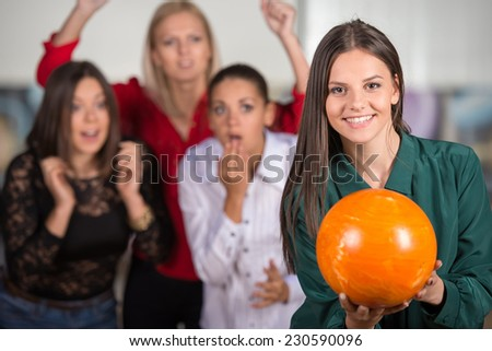 Portrait of a girl who is getting ready to throw the ball against the background of her friend. - stock photo