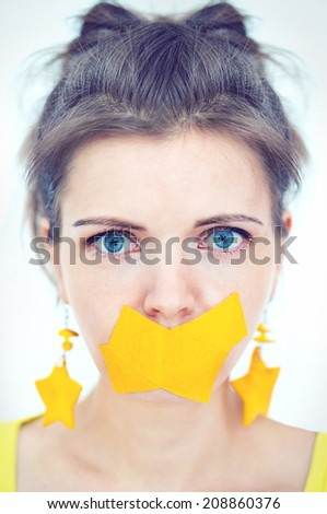 Portrait of a girl with blue eyes and yellow tape taped mouth closeup for advertising, printing, banner - stock photo