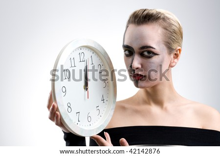 Portrait of a girl with clock on gray