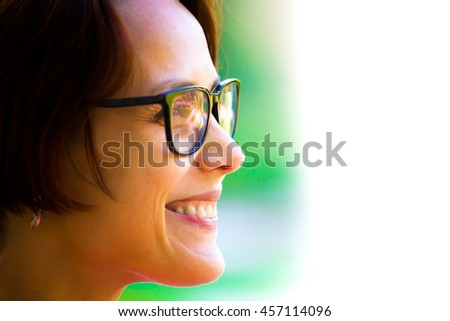 Portrait of a girl with dark hair in stylish glasses in daylight.