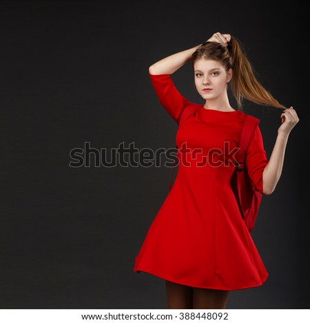 Portrait of a girl with long hair in a red dress
