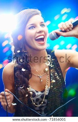 Portrait of a glamorous girl holding a mike and singing
