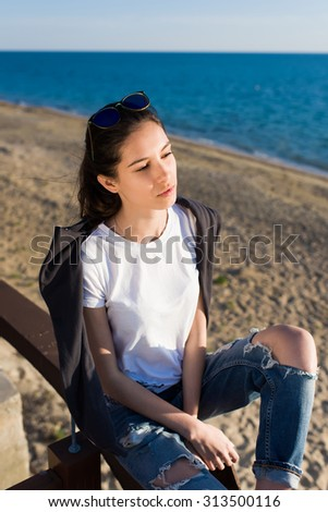 Portrait of a glamorous hipster girl enjoying sunny spring day outdoors on the beach, young attractive woman dressed in a trendy clothes relaxing after promenade along the seashore at afternoon - stock photo