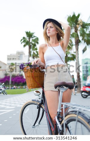 Portrait of a glamorous tourist woman enjoying summer vacation riding on retro bicycle with a basket of flowers, trendy female cyclist standing in the street with her vintage bike and looking aside - stock photo