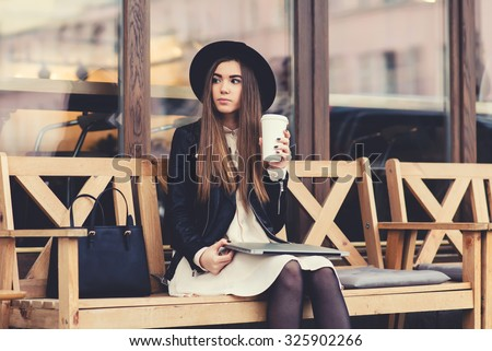 Portrait of a glamorous young woman holding on her knees portable laptop computer while sitting on a wooden bench, stylish female drinking coffee while relaxing after work on net-book during free time - stock photo