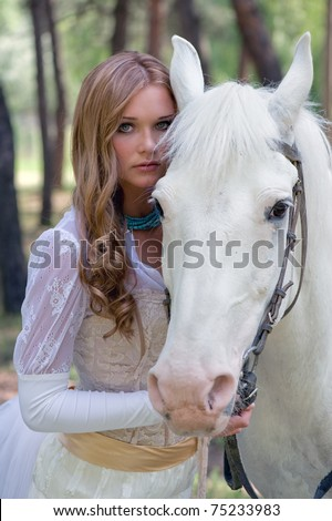 Portrait of a glamour young woman with wavy long hairs in refined white clothing and beautiful horse somewhere in a park - stock photo