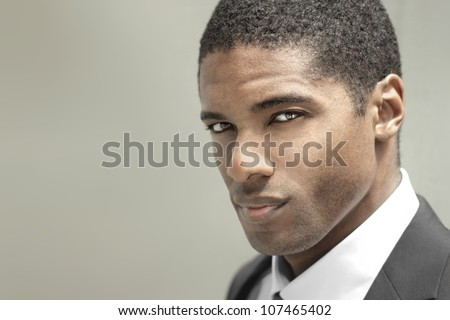 Portrait of a good looking handsome young businessman in black suit - stock photo