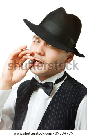 Portrait of a good looking man dressed like a gangster smoking cigar