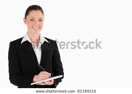 Portrait of a good looking woman in suit writing on a notebook while standing against a white background - stock photo