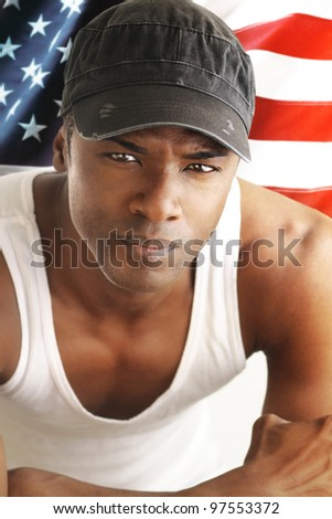 Portrait of a good looking young man against American flag backdrop - stock photo