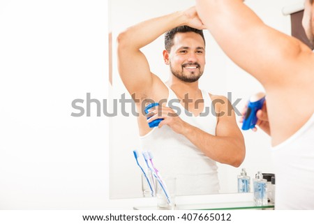 Portrait of a good looking young man putting some deodorant on his armpit in front of a bathroom mirror and smiling - stock photo