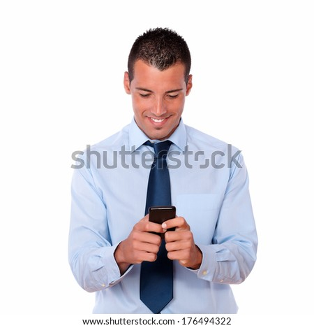Portrait of a gorgeous adult man on blue shirt and tie texting with his cellphone while standing on isolated background - stock photo