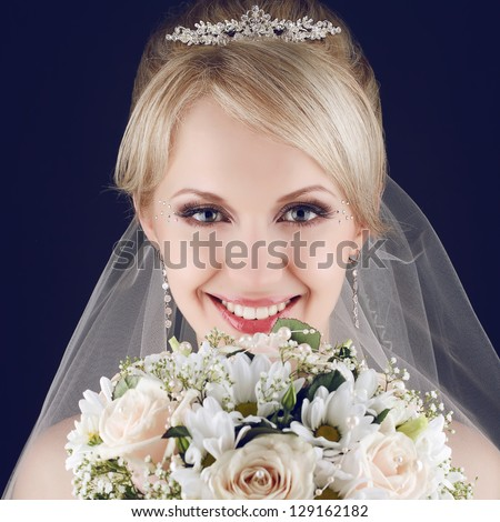 Portrait of a gorgeous blonde bride with splendid shiny smile holding a wedding bouquet of roses and camomiles and posing over dark-blue background. Close up. Studio shot - stock photo