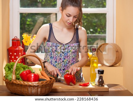 Portrait of a gorgeous brunette preparing healthy meal in the kitchen. - stock photo