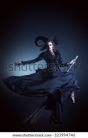 Portrait of a gorgeous brunette witch flying on a broom over black background. Halloween.  - stock photo