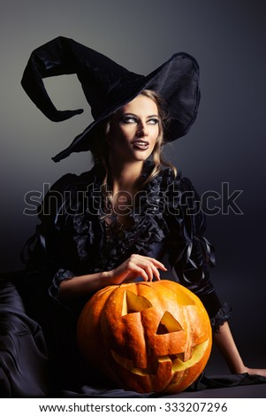 Portrait of a gorgeous brunette witch in black dress and a hat sitting with pumpkin over black background. Halloween.  - stock photo