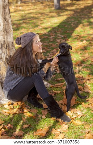 Portrait of a gorgeous brunette woman in the autumn park playing with stray dog. Shallow depth of field - stock photo