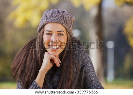 Portrait of a gorgeous brunette woman in the autumn park. Shallow depth of field - stock photo