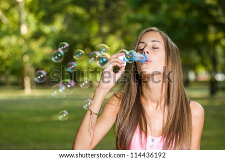 Portrait of a gorgeous dreamy young teen blowing soap bubbles.
