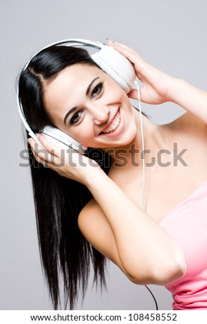 Portrait of a gorgeous fashionable young brunette listening to music.