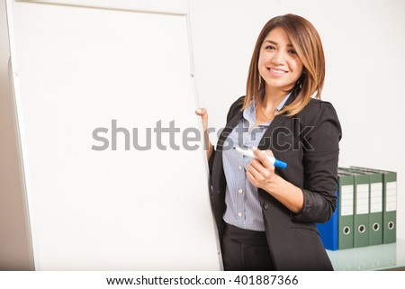 Portrait of a gorgeous Hispanic woman teaching Spanish and standing next to a flip chart - stock photo