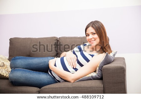 Portrait of a gorgeous Hispanic young woman relaxing at home and enjoying her pregnancy