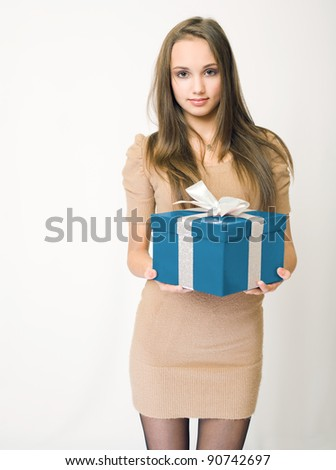 Portrait of a gorgeous slender young brunette model holding shiny colorful gift box. - stock photo