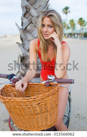 Portrait of a gorgeous woman dressed in fashionable swimwear sitting on her vintage bike enjoying rest after riding,attractive female in bikini posing for the camera on the beach in California - stock photo
