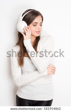 Portrait of a gorgeous young brunette listening to music in headphones. - stock photo