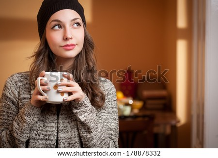 Portrait of a gorgeous young brunette relaxing with cup of hot beverage. - stock photo