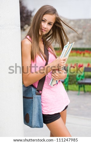 Portrait of a gorgeous young brunette student girl in the park.