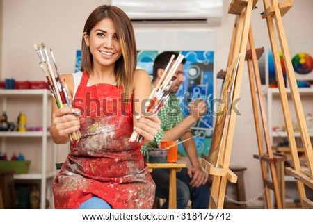 Portrait of a gorgeous young brunette wearing an apron and holding a bunch of paintbrushes in an art class - stock photo