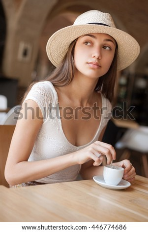 Portrait of a gorgeous young brunette woman with espresso.