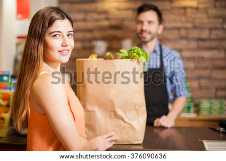 Portrait of a gorgeous young Hispanic woman buying some groceries at a supermarket - stock photo