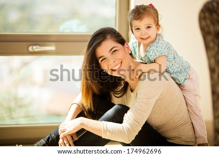 Portrait of a gorgeous young mother and her little girl smiling in the living room - stock photo