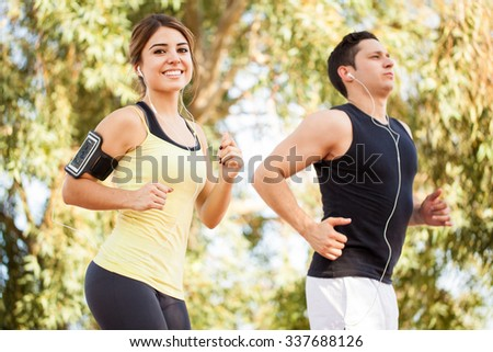 Portrait of a gorgeous young woman listening to music with a smartphone and earbuds and running alongside her boyfriend - stock photo