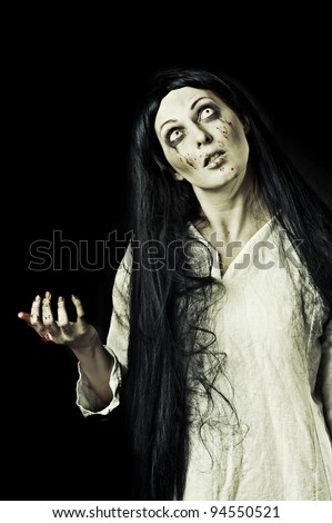 Portrait of a gory bloody and scary zombie woman on black background - stock photo