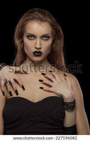Portrait of a gothic woman with hands of vampire on her body on black background.Halloween - stock photo