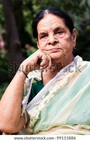 portrait of a graceful senior indian woman, senior Indian woman sitting in the lawn or garden - stock photo