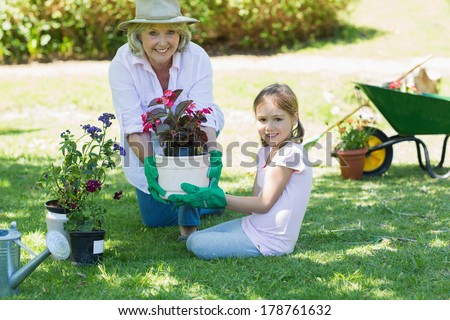 Portrait of a grandmother and granddaughter engaged in gardening - stock photo