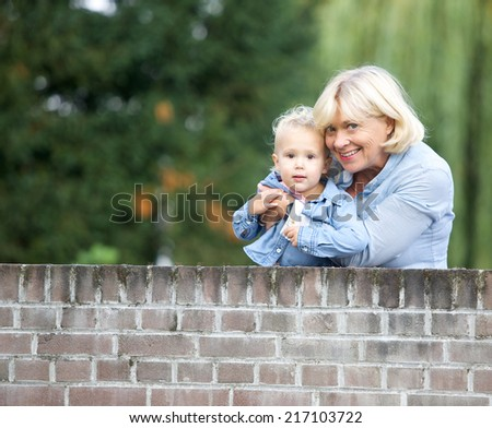 Portrait of a grandmother smiling with baby girl outdoors - stock photo