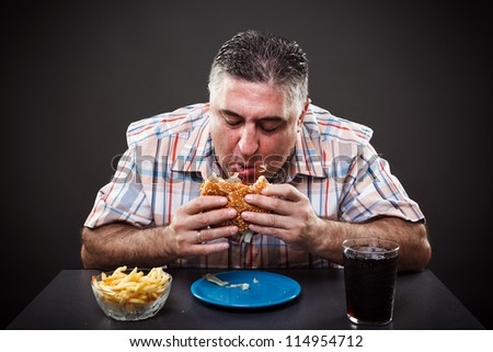 Portrait of a greedy fat man eating burger on gray background - stock photo