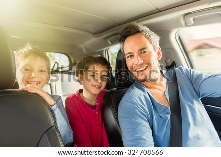 Portrait of a grey hair father with beard and his two kids in the car. The ten years old brother and sister are sitting in the back, they are wearing long sleeves shirts. The father have his seat belt - stock photo