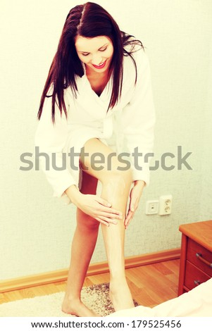 Portrait of a groomed woman dressed in a dressing-gown, lubricating her leg in the bedroom. - stock photo