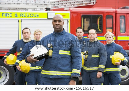 Portrait of a group of firefighters by a fire engine - stock photo